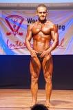 O halterofilista masculino dobra seus músculos para mostrar seu físico Imagens de Stock