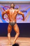 O halterofilista masculino dobra seus músculos para mostrar seu físico Fotografia de Stock
