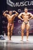O halterofilista mostra sua pose dobro dianteira do bíceps na fase Fotos de Stock Royalty Free