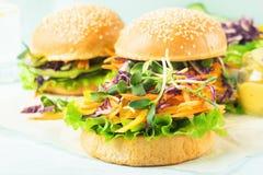 O hamburguer do vegetariano com os vegetais crus frescos fecha-se acima em um fundo azul Conceito saudável comer Foco seletivo foto de stock