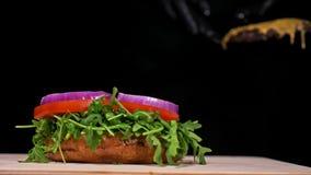 O hamburguer está cozinhando no fundo preto em luvas pretas do alimento Bolo muito gostoso do ar e carne marmoreada Restaurante o filme