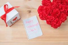 O Handmaid floresce na caixa com o cartão do Valentim no contexto marrom Imagens de Stock Royalty Free