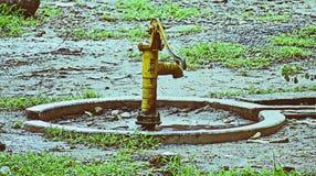 O handpump amarelo na terra gramínea verde Fotografia de Stock