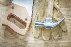 O handsaw afiado das luvas protetoras de martelo de garra na placa de madeira cons fotografia de stock