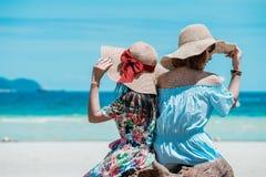 O Hawaiian vestindo da mulher asiática nova com chapéu e óculos de sol está feliz quando vão à praia imagens de stock royalty free