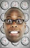 O Headshot de vidros vestindo preocupados do homem com vário fuso horário cronometra no fundo Fotos de Stock Royalty Free