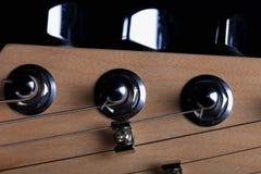 O headstock de uma guitarra elétrica no fundo preto imagens de stock royalty free