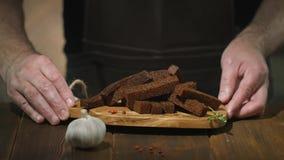 O hef do ¡ de Ð põe a placa de corte com pão torrado ou os petiscos fritados da cerveja sobre a tabela de madeira filme