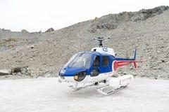 O helicóptero da aterrissagem de Helicóptero Linha Empresa no pico de montanha snowcapped em torno do cozinheiro da montagem de A Foto de Stock