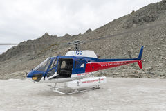 O helicóptero da aterrissagem de Helicóptero Linha Empresa no pico de montanha snowcapped em torno do cozinheiro da montagem de A Foto de Stock Royalty Free