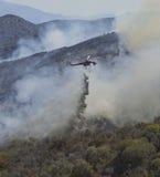 O helicóptero deixa cair retardent no fogo Fotografia de Stock Royalty Free