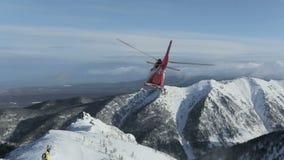 O helicóptero deixou esquiadores na inclinação da montanha e voou aumentando uma nuvem da neve filme