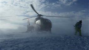 O helicóptero deixou esquiadores na inclinação da montanha e voou aumentando uma nuvem da neve video estoque