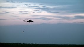 O helicóptero do fogo da carga com a concha suspendida do vertedouro está voando do reservatório