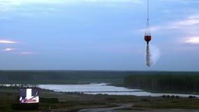O helicóptero do fogo da carga com a concha suspendida do vertedouro está voando do reservatório filme