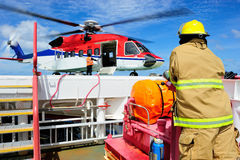 O helicóptero no helideck com o guarda-fogo que está perto Foto de Stock Royalty Free