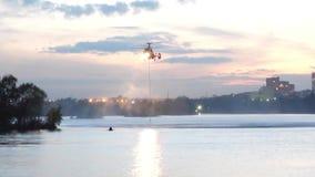 O helicóptero recolhe a água no rio para extinguir um fogo O serviço de salvamento e os sapadores-bombeiros extinguem o fogo video estoque