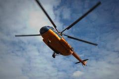 O helicóptero voa contra o céu com nuvens Imagem de Stock