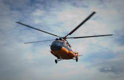 O helicóptero voa contra o céu com nuvens Fotografia de Stock Royalty Free