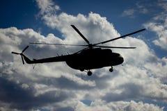 O helicóptero voa contra o céu com nuvens Imagens de Stock