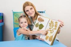 O herbário de exame de cinco anos da menina e da mãe mostra em uma das folhas no álbum, e olhado no quadro Fotos de Stock