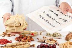 O herbalist asiático faz uma prescrição. Fotos de Stock