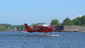 O hidroavião vermelho desliza ao longo das ondas contra o contexto de barcos de mar filme