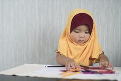 O hijab vestindo pequeno asiático da criança/bebê está tendo o divertimento que aprende usar lápis imagens de stock royalty free