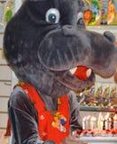O hipopótamo em um fato-macaco vermelho que guarda levar um bolo com queimadura pode fotografia de stock royalty free