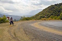 O Hitchhiker instala o sinal na curvatura perigosa da estrada Imagens de Stock