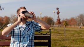 O homem à moda e na moda novo em vidros pretos senta-se em um café bebendo do banco e na fala no telefone, close-up, cópia filme