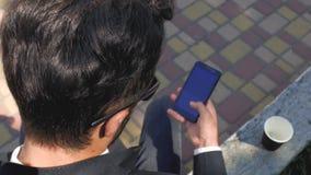 O homem à moda em um terno clássico e em óculos de sol senta e olha o telefone Vista de acima Homem de neg?cios de sorriso 4K 4K filme