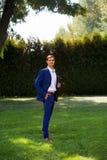 O homem à moda em uma asseguração do terno abotoa-se em seu revestimento que prepara-se para sair imagens de stock