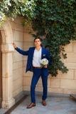 O homem à moda em uma asseguração do terno abotoa-se em seu revestimento que prepara-se para sair imagem de stock