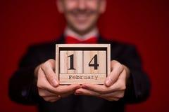 O homem à moda no calendário de madeira da posse do terno, ajustou-se o 14 de fevereiro com fundo vermelho, foco no calendário Imagens de Stock