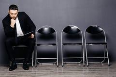 O homem à moda novo com barba está preparando-se para a entrevista É em um terno, sentando-se no salão na cadeira, esperando e ob fotos de stock