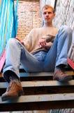 O homem à moda novo senta-se em escadas perto da parede de tijolo. Fotos de Stock Royalty Free