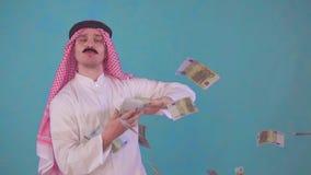 O homem árabe alegre do retrato com um bigode e uma roupa tradicional com Audi, joga o dinheiro vídeos de arquivo