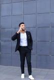 O homem árabe considerável fala no telefone esperto no centro de negócios Fotografia de Stock