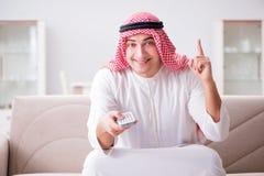 O homem árabe novo que olha a tevê sentar-se no sofá fotos de stock