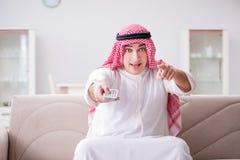O homem árabe novo que olha a tevê sentar-se no sofá imagem de stock
