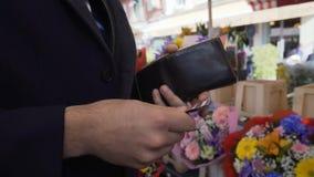 O homem ávido ou econômico não pode parte com dinheiro para pagar pelo ramalhete no florista vídeos de arquivo