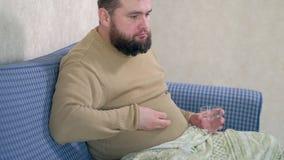 O homem é água potável com os comprimidos, sentando-se na cama video estoque