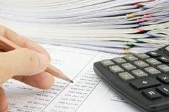 O homem é conta de exame com lápis e calculadora foto de stock royalty free