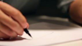 O homem é de tiragem ou de escrita na folha de papel branca Tiro macro do negócio que veste uma camisa e que escreve no papel atr filme