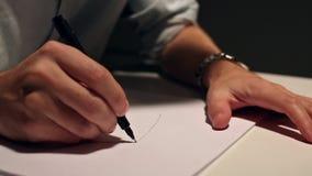 O homem é de tiragem ou de escrita na folha de papel branca Tiro macro do negócio que veste uma camisa e que escreve no papel atr video estoque