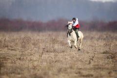 O homem é em pelo montando um cavalo decorado antes de uma corrida de cavalos da celebração do esmagamento imagens de stock