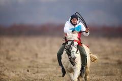 O homem é em pelo montando um cavalo decorado antes de uma corrida de cavalos da celebração do esmagamento imagens de stock royalty free