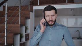 O homem é estando e de fala pelo telefone celular com colegas e sócio sobre o sucesso no negócio video estoque