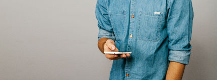 O homem é ocupado no telefone Site do slider Camisa do azul da sarja de Nimes Imagens de Stock Royalty Free